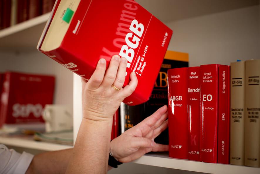 Rechtsanwaeltin mit Buch beim Bücherregal-Mag. Putz-Haas & Riehs-Hilbert in 1030 Wien